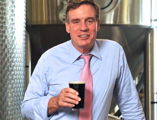 (US Sen. Mark Warner enjoys a pint at O'Connor Brewing Company. Photo by Kathy Keeney)